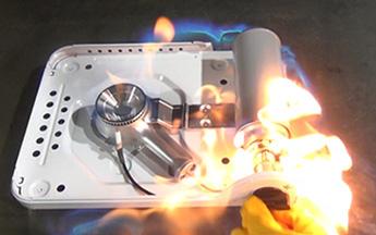 ステムの根元付近からガス漏れが発生しているカセットボンベをカセットこんろへ取り付けて、数秒後に点火を行ったところ、カセットこんろとカセットボンベの接合部の周辺から漏れて充満していたガスに引火して炎が上がっている。
